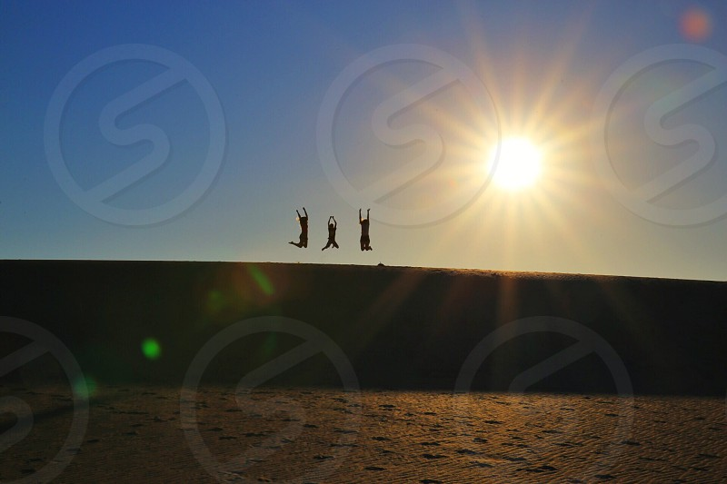 silhouette of three people jumping photo