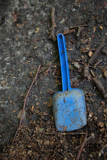 Ground woods forest play spade shovel blue plastic materials background backgrounds wallpaper dirt earth down laying mud muddy tree abstract symbolizing symbol garden gardener work worker kids playground alone abandoned photo