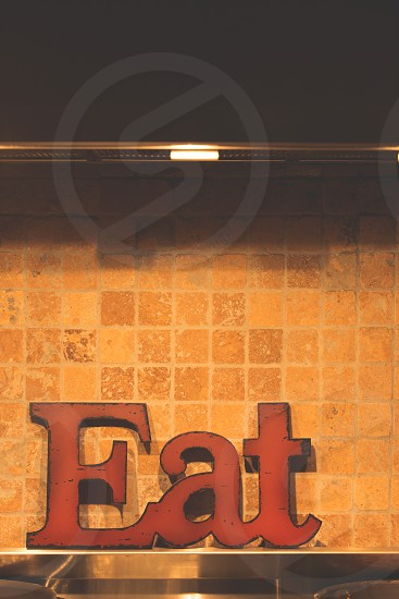Eat sign sitting on the back of an oven range against a tile backdrop. photo