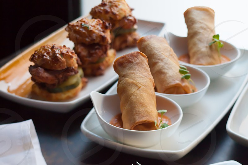 3 canape pastry with pickle beside 3 spring rolls on cup photo