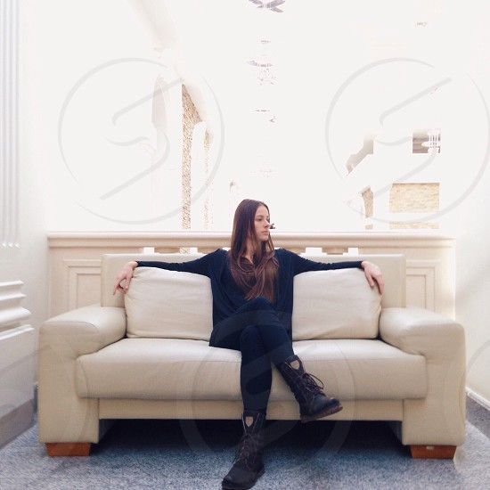 woman with brown long hair in black long sleeved shirt black pants and black boots sitting on white cushion couch photo