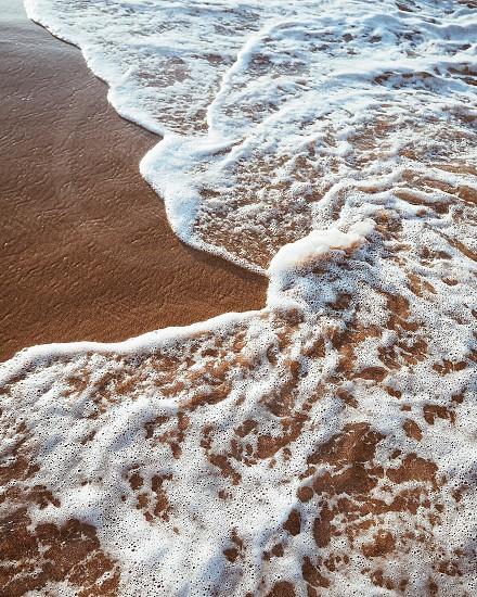 white ocean foam in brown sand beach during daytime photo