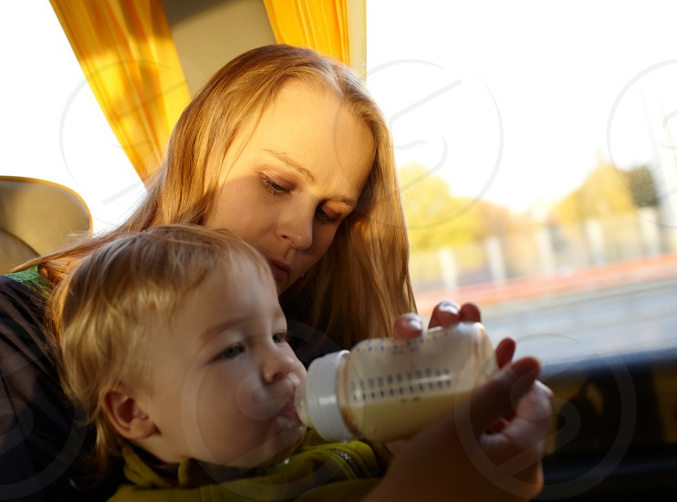 Young mother is feeding her two year old son with milk while they are travelling by intercity bus. Close up portraits with natural light. photo