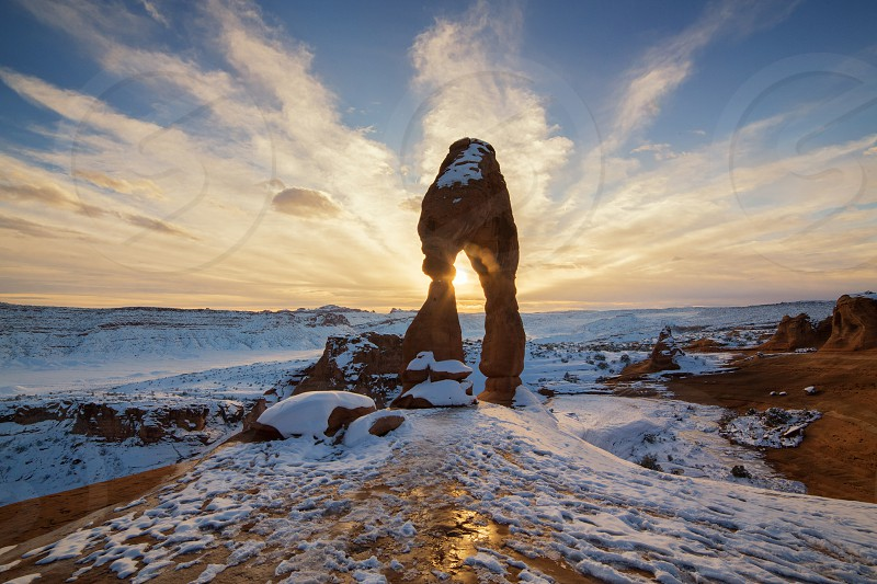 This is the picture of Delicated Arch with snow during sunset at Arches National Park Utah. photo