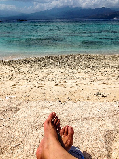 Bare feet on the beach Enjoying the beach sand sunbathing suntan  photo