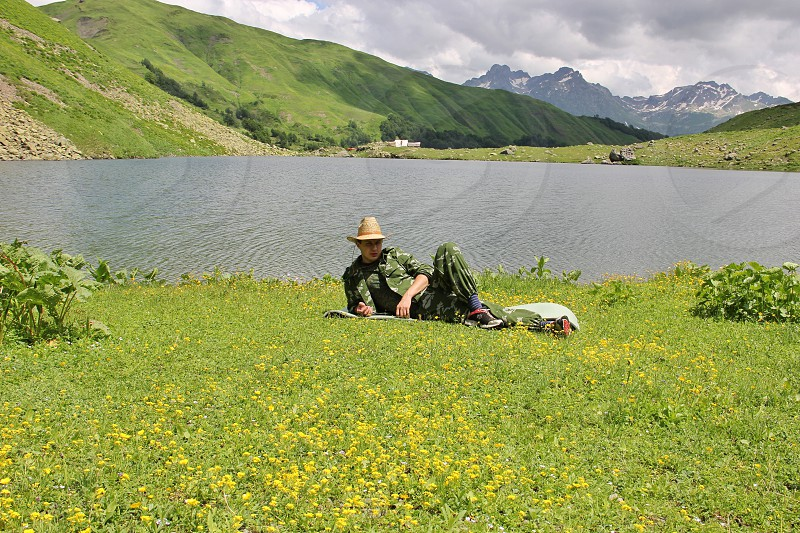 man in green jumpsuit and beige sun hat lying with cross legs on grass near placid body of water during daytime photo