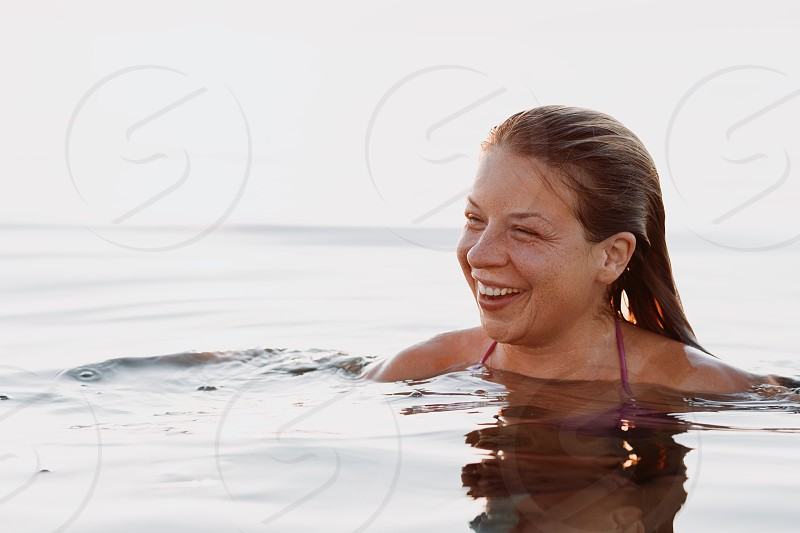 Young woman floating on the water surface in the sea photo