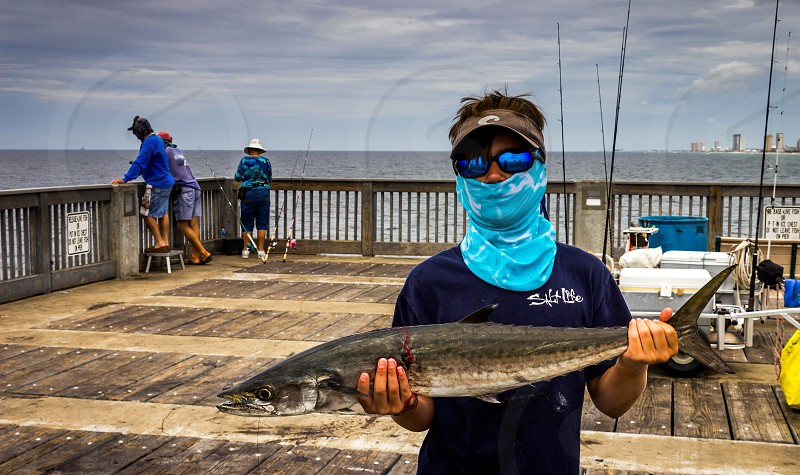 A moment captured when a local fisherman on the Florida coast reeled in a large catch of the day.  photo