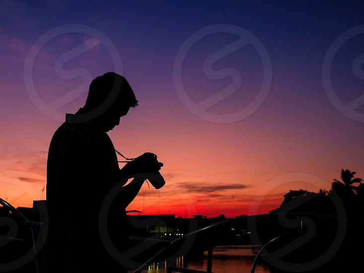 Photographer shooting photo sunset at dusk Thailand. photo