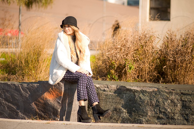woman in white trench coat and black and white checked pants sitting on black and gray rock in tilt shift lens photo