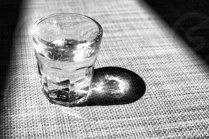 Black and white small glass of liquor grappa glass traditional Italian drink sparkles in glass framed with shadow photo