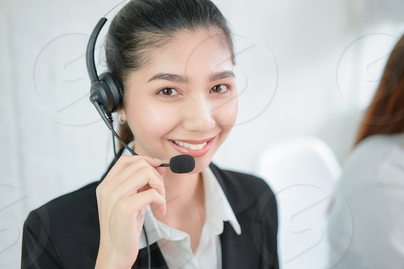 Smiling Asian businesswoman consultant wearing microphone headset of customer support phone operator at workplace. photo