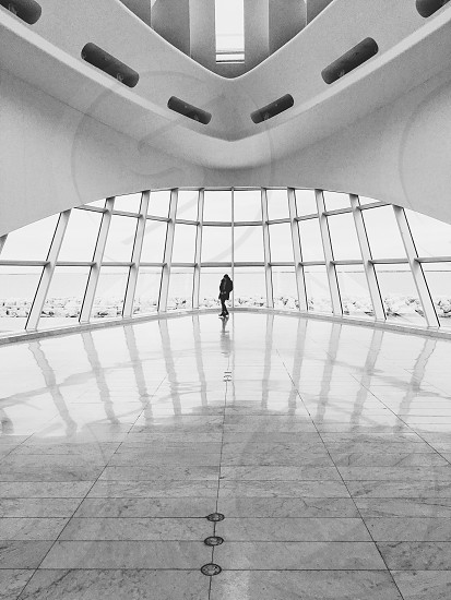 grayscale photo of person standing near glass panel wall of white concrete building with gray tile floor photo