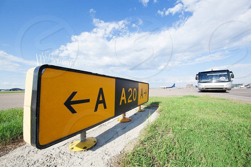Yellow road sign in the airport bus and airplane in the background photo