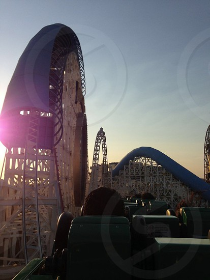 white metal roller coaster with blue sky view photo