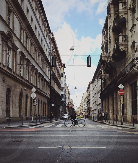 person in black jacket riding bicycle and crossing on street under blue and white sunny cloudy sky photo
