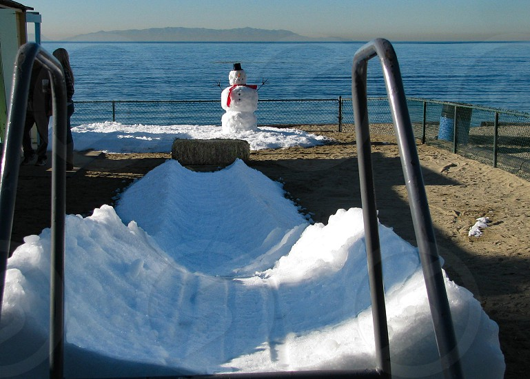 It's a southern California Christmas with a snowman made of snow from the mountains beside the Pacific Ocean in southern California. Also an ice slide for children at a preschool makes it winter at the beach. photo