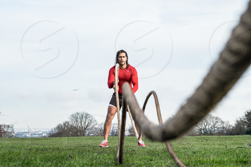 Asian Athlete with long dark hair wearing a red sports too doing a rope workout outside in the park photo