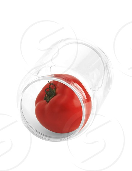 tomato in a glass jar isolated on white background photo