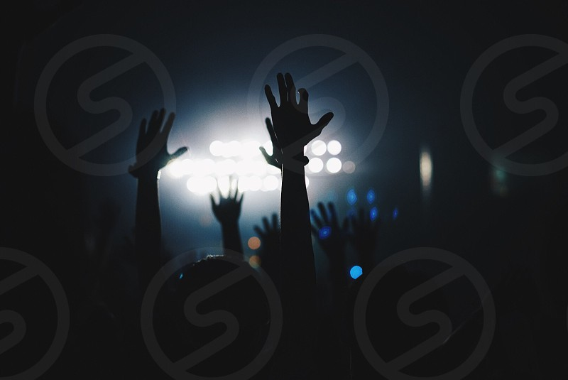 silhouette of people inside concert hall with their hands raised up photo