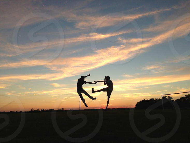 """Silhouetted"" Two friends jump around with the daylight that is left. photo"