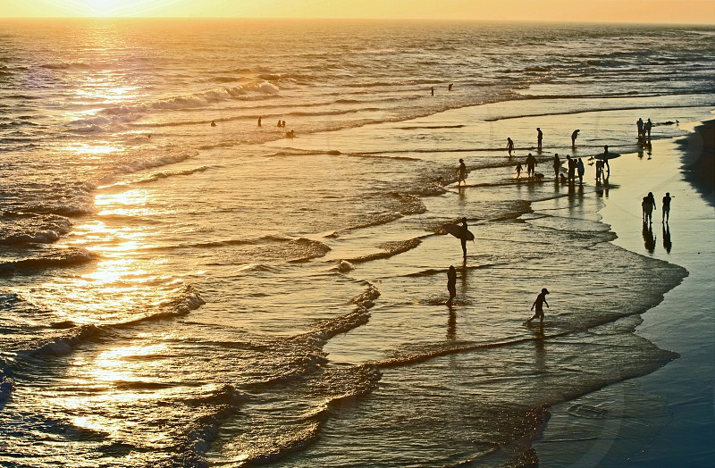 Taken from above the ocean looks golden at sunset as people play on the beach and wade in the water. photo