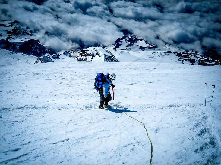 Man mountain climbing to  Mt. Rainier s summit. Ice Axe Mountain peak above the clouds Snow   photo