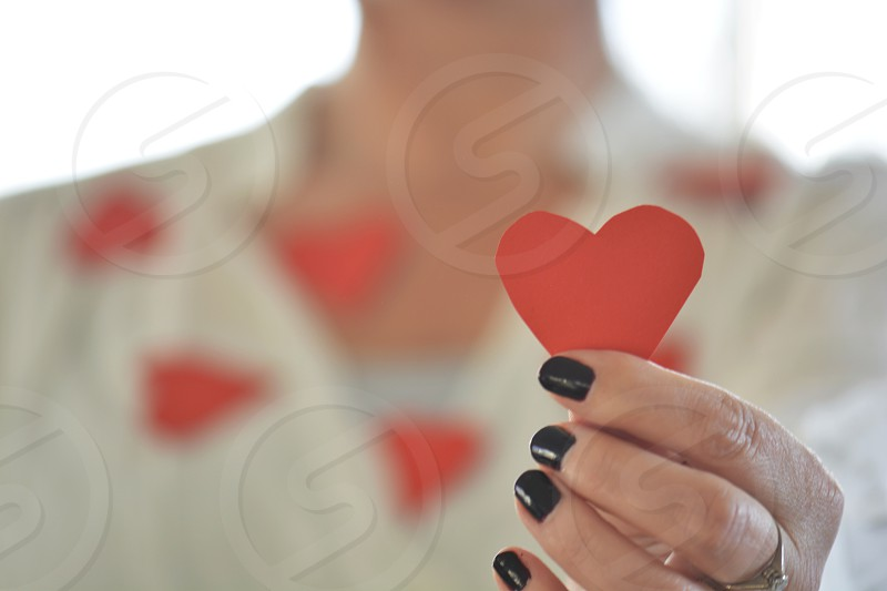 woman in black manicure holding red heart cutout photo