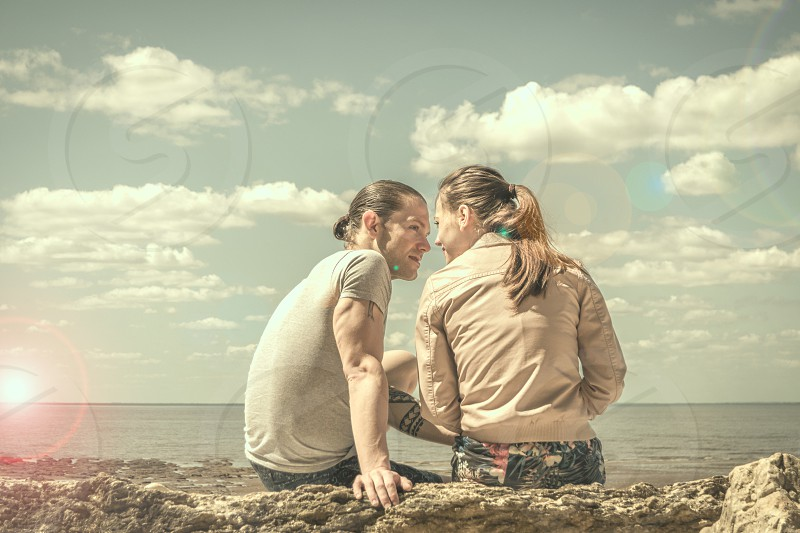Young couple sitting on a rock at the seaside locked in eye contact before kissing photo
