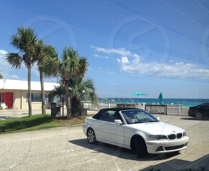 white convertible bmw car on grey parking lot under blue sky photo