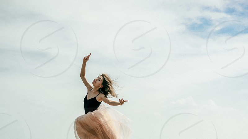 athletic woman stretching jumping against the sky a warm summer day outdoor exercise photo