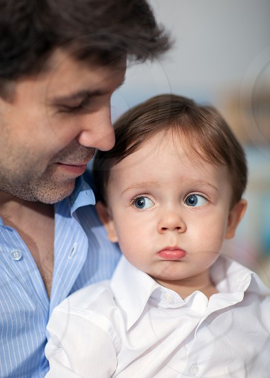 Portrait of son and father. Boy is pouting. photo