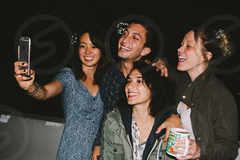 A group of friends at a party take a selfie photo