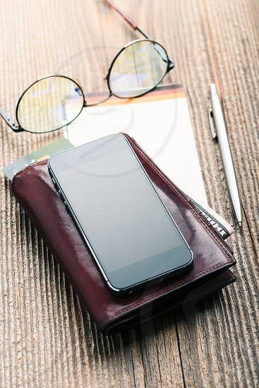 Smartphone with blank screen wallet dollar banknotes debit credit cards and notebook on wooden table. View from above. Portrait orientation photo