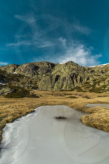 A little ice lake between the mountains. photo
