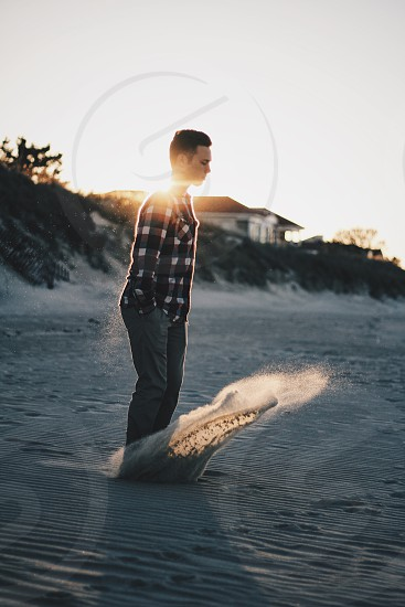 man in black and white checkered long sleeves kicking sand photo