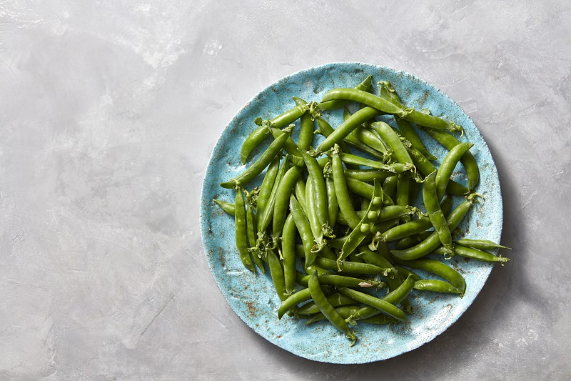 Top view of a blue ceramic plate with natural young green peas in sticks on a gray marble kitchen background. Copy space. photo