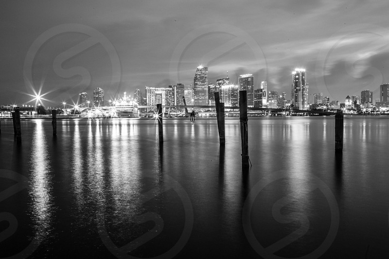 clouds in sky over illuminated city skyline at night in black and white photo