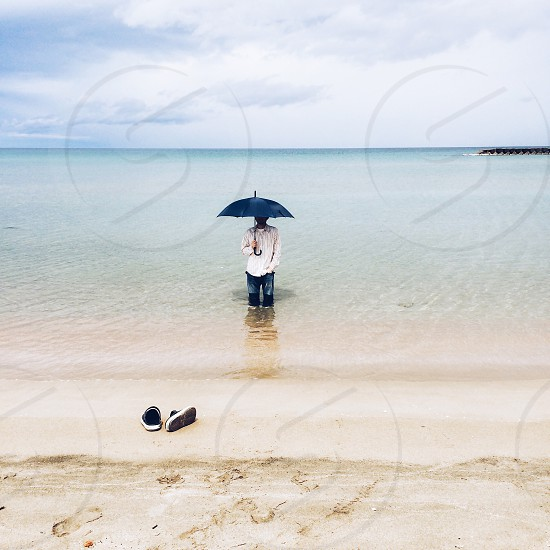 man carrying umbrella on beach side photo