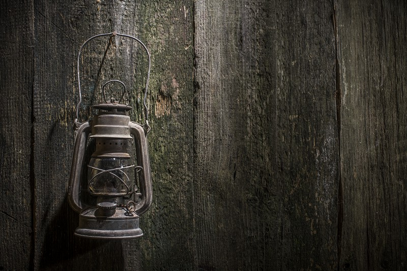 Old gas lantern on wood at darkness photo