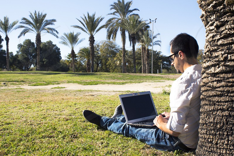 man sitting on grass field leaning on palm tree with gray laptop computer on leg photo