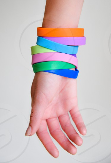 orange pink blue purple and green silicone bands on person's wrist photo