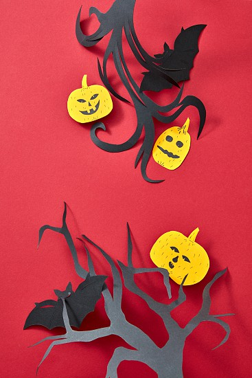 Halloween composition of handcraft paper pumpkins bats and trees on a red background with copy space. Flat lay photo