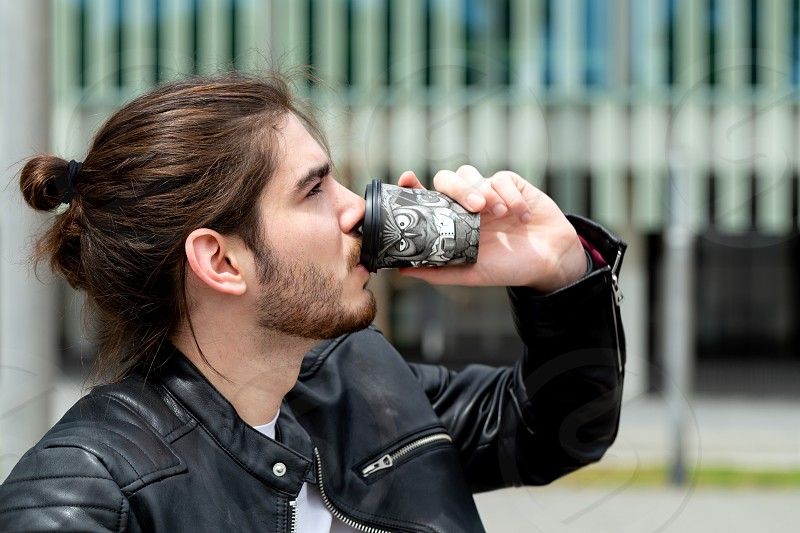 Portrait of a handsome fashionable hipster man in a black leather jacket drinking tea or coffee from a black takeaway paper cup outside. photo