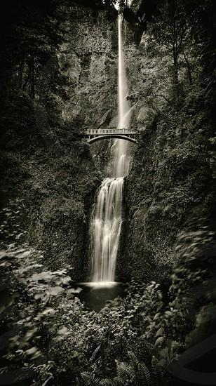 metal bridge on top of waterfalls in grayscale photography photo