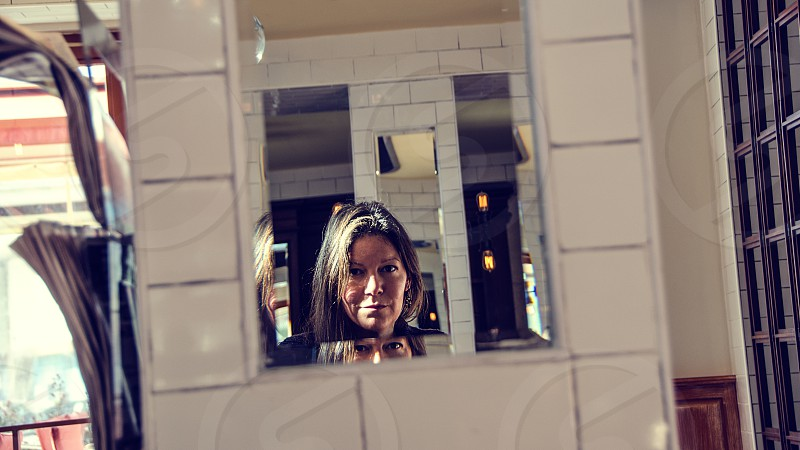 A woman looking into a mirror. photo