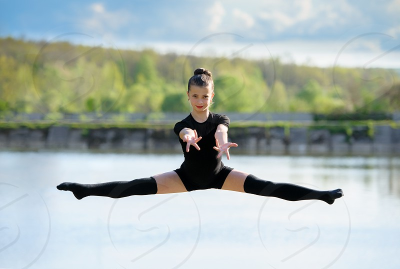 Smiling young gymnast is jumping in split and floating above the earth. photo