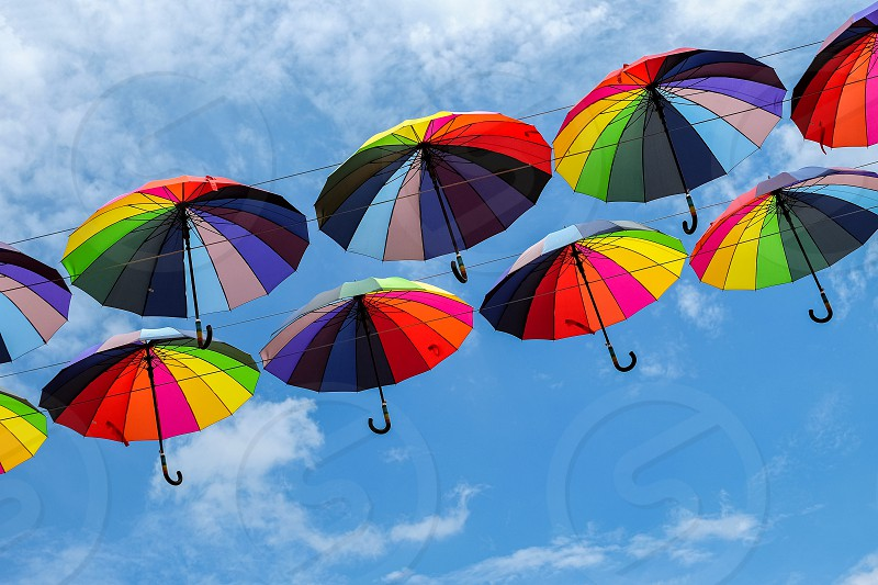 Two rows of rainbow umbrellas against the sky. photo