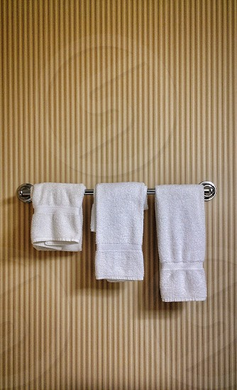 three white hand towels hanging on a metal bathroom bar on a brown striped wall photo