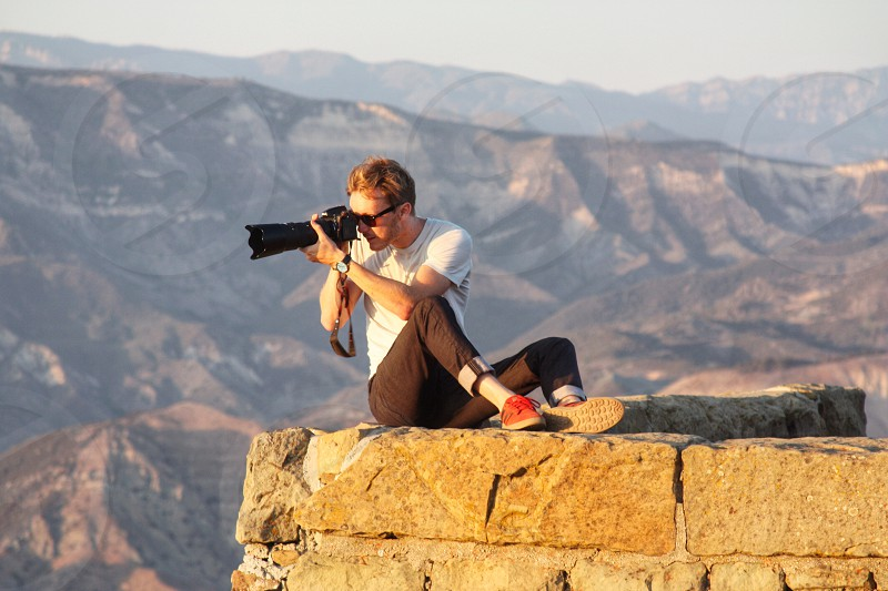 man in plateau aiming his camera photo